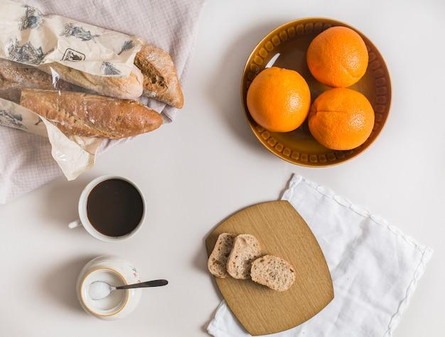 Rebanadas de pan; naranjas enteras taza de té y leche en polvo sobre fondo blanco Foto gratis