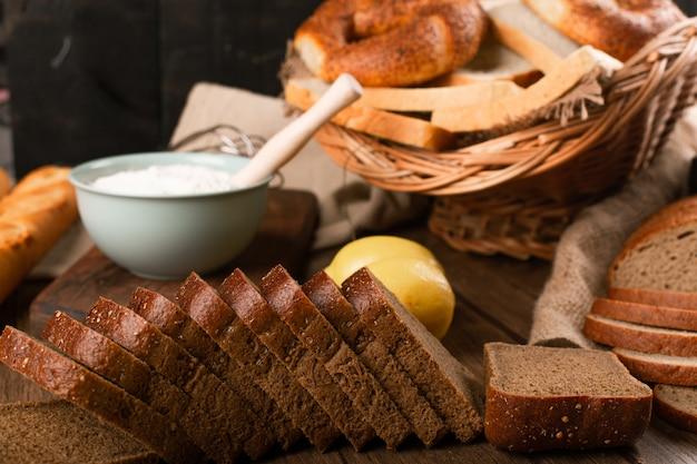 Rebanadas de pan con panecillos y tazón de harina Foto gratis