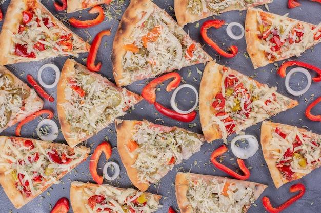 Rebanadas de pizza sabrosa en azul con aros de cebolla y pimiento. Foto gratis