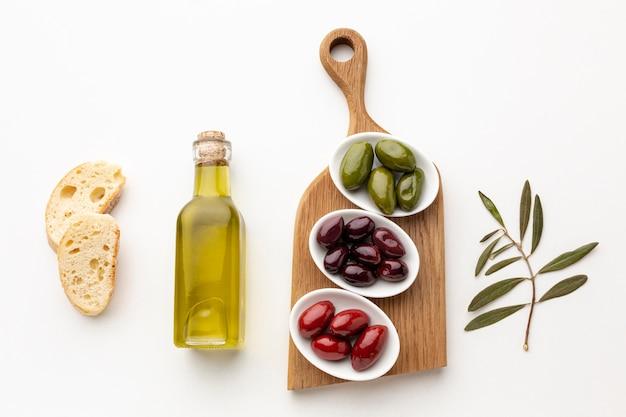 Rebanadas planas de pan y aceitunas verde rojo púrpura con botella de aceite de oliva Foto gratis