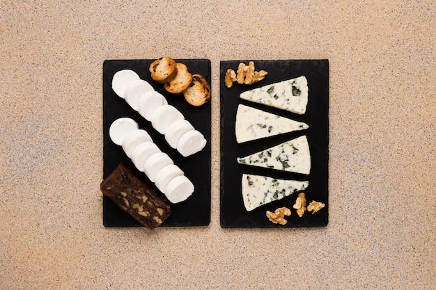 Rebanadas de queso gorgonzola y nuez con queso de cabra; queso marrón y pan en piedra pizarra negra sobre papel tapiz texturado Foto gratis
