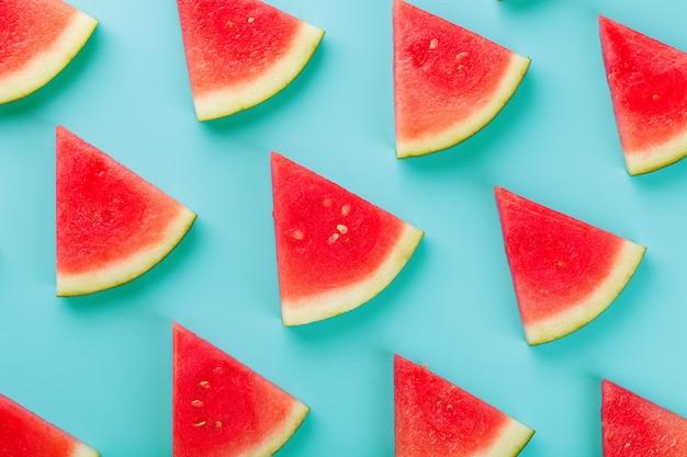Rebanadas de rebanadas frescas de sandía roja y amarilla en azul. Foto Premium