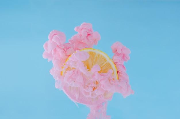 Rebane el limón con el foco parcial de disolver el color de cartel rosado en agua en fondo azul. Foto Premium