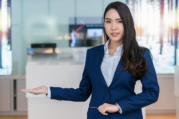 Recepción asiática que da la bienvenida al cliente al mostrador de la sala de exhibición de automóviles para el servicio al cliente. Foto Premium