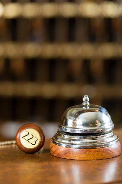Recepción, timbre del hotel y llave en el escritorio Foto Premium