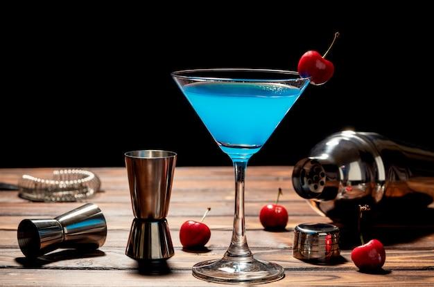 Receta de martini azul coctel colorido con accesorios de cereza y barman rojos en la mesa de madera Foto Premium