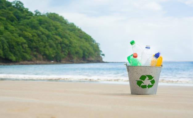 Reciclar, cesta con botella de plástico en la playa. Foto Premium