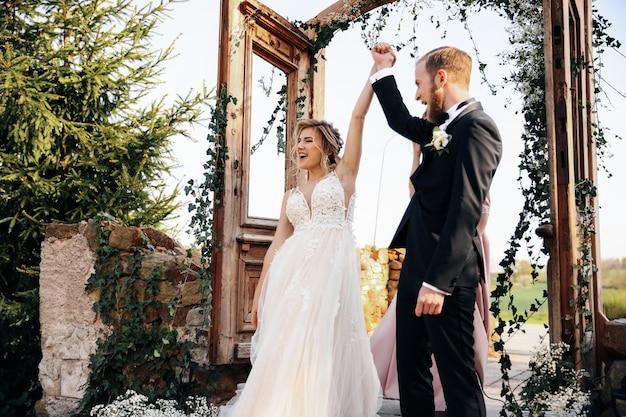 Recién casados levantando las manos después de la ceremonia de boda terminada Foto gratis