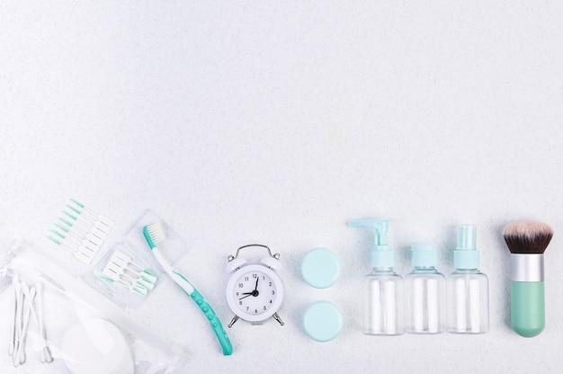 Recipientes de plástico, cepillo de dientes y reloj despertador para viajes. Foto Premium