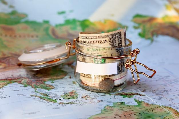 Recoger dinero para viajar. lata de vidrio como hucha con ahorros en efectivo (billetes y monedas) en el mapa Foto Premium