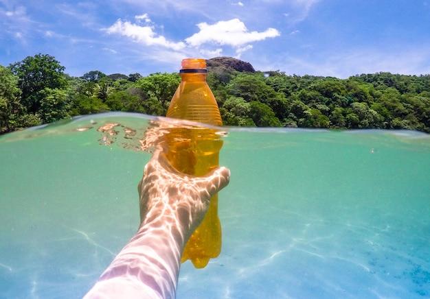 Recogiendo una botella de plástico del ocwan, recicla Foto Premium