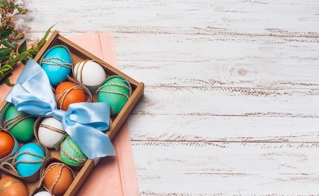 Recolección de huevos brillantes en caja en papel artesanal rosado cerca de las plantas Foto gratis