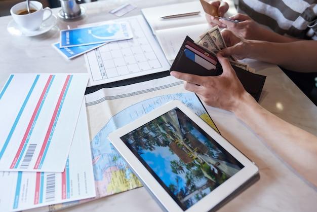 Recorta pareja irreconocible contando dinero para vacaciones Foto gratis