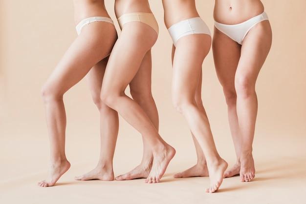 Recortar figuras femeninas descalzas en ropa interior de pie uno detrás del otro Foto gratis