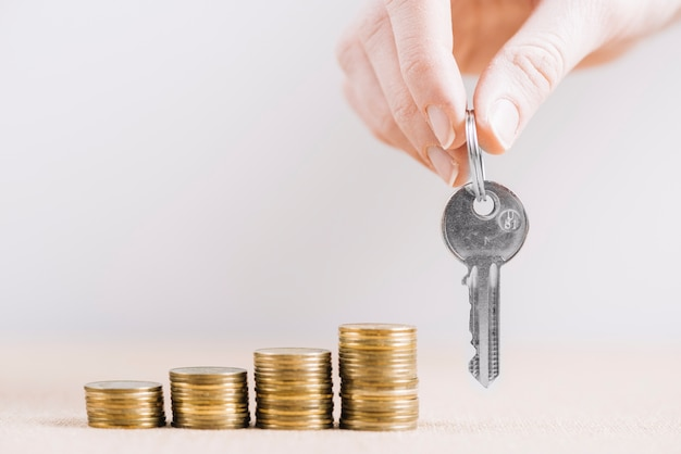 Recortar la mano con la llave cerca del dinero Foto Premium
