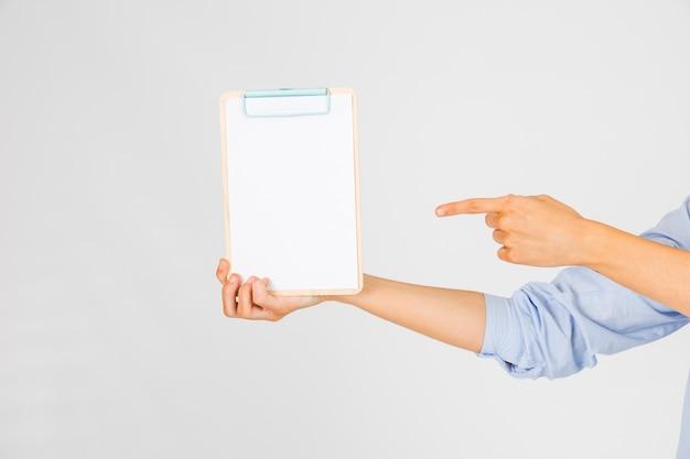 Recortar las manos apuntando al portapapeles Foto gratis
