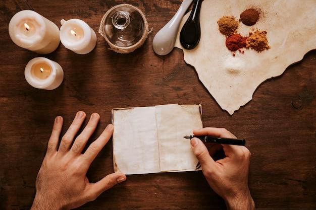 Recortar manos escribiendo cerca de velas e ingredientes Foto gratis