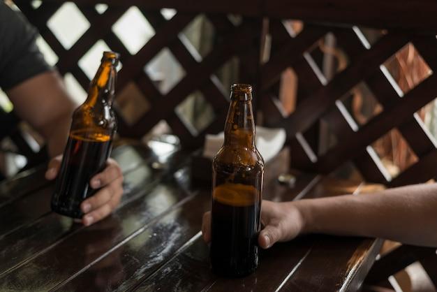 Recortar las manos manteniendo la cerveza en la mesa Foto gratis