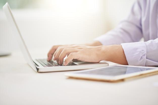 Recortar manos masculinas usando laptop Foto gratis