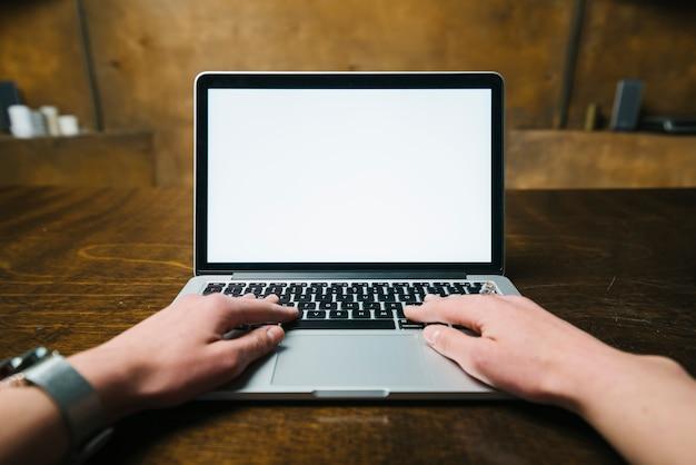 Recortar las manos usando la computadora portátil moderna Foto gratis