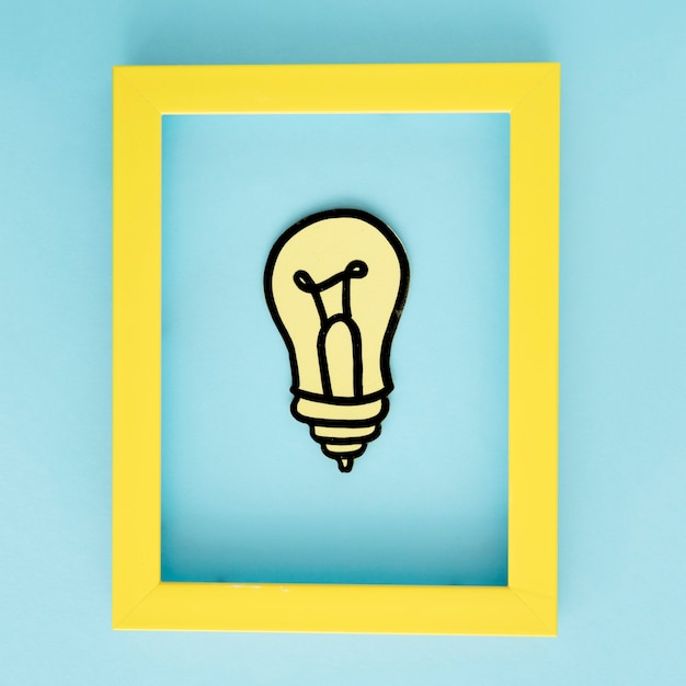 Recorte de papel de bombilla amarilla con marco de borde amarillo sobre fondo azul Foto gratis
