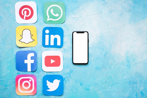 Recortes de papel de iconos de redes sociales dispuestos cerca de teléfono inteligente Foto gratis