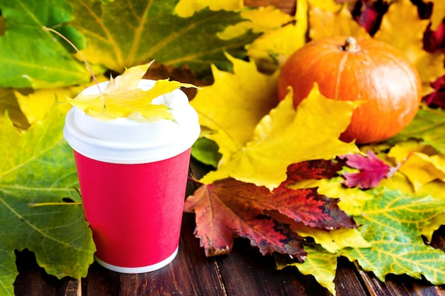 Red coffee to go cup witn marple leaf and pumpkin Foto Premium