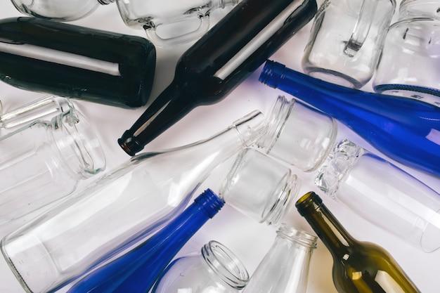 Reduzca la reutilización reciclan. clasificación de residuos. las botellas de vidrio coloridas vacías están preparadas para reciclar. proteger el medio ambiente. vista superior Foto Premium