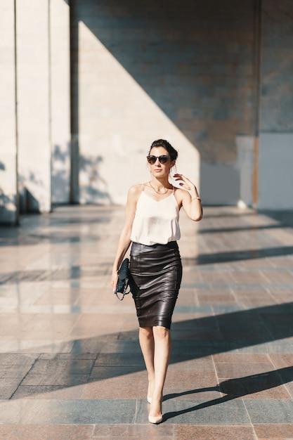 Refinada mujer joven en falda de cuero y blusa de seda caminando confiada cerca de un edificio. Foto gratis