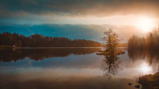Reflejo de los árboles en un lago bajo el increíble cielo colorido capturado en suecia Foto gratis
