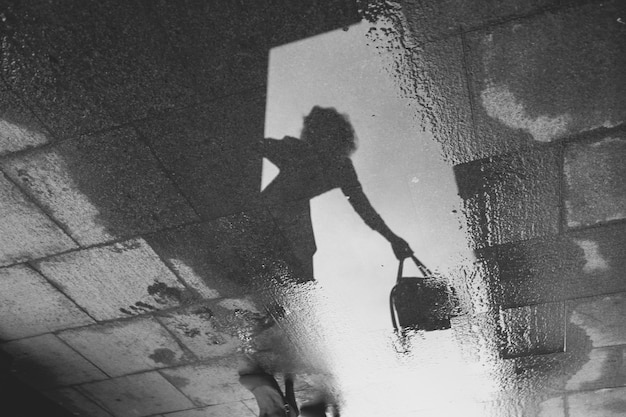 Reflejo de una niña con una bolsa en la mano en un charco sobre un pavimento de piedra. en blanco y negro Foto Premium