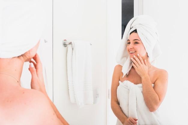Reflexión de hermosa mujer mirando en bata de baño con una toalla sobre su cabeza Foto gratis