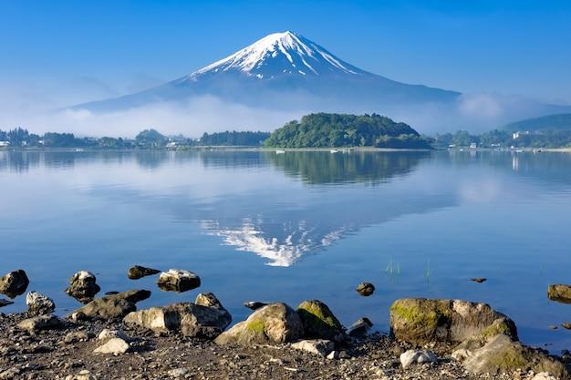 Reflexión del monte. fuji con primer plano de la orilla de roca, lago kawaguchiko, yamanashi Foto Premium