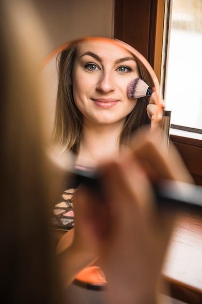 Reflexión de una mujer sonriente que aplica colorete en su cara Foto gratis