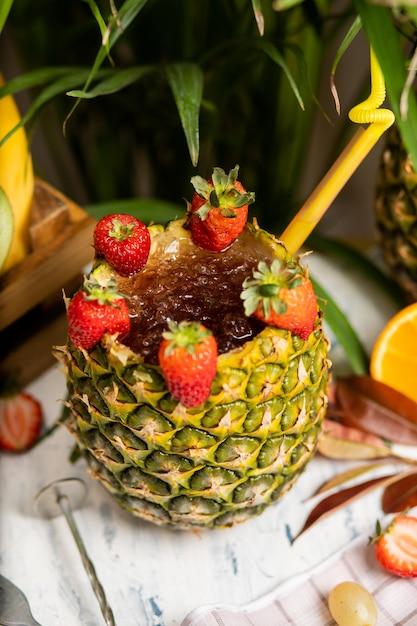Refrescante cóctel alcohólico de verano, margarita con hielo picado y frutas cítricas dentro de la piña con fresas en la mesa de la cocina Foto gratis