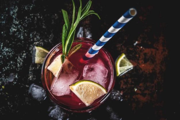 Refresco alcohólico cóctel de arándano rojo y limón con romero y hielo, dos vasos, copyspace oscuro vista superior Foto Premium