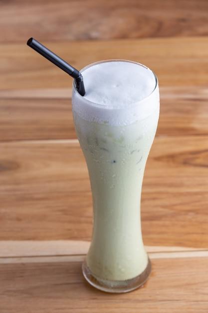 Refresque el té verde en un vaso alto colocado en el piso de tablones. Foto gratis