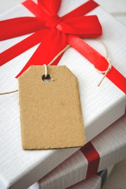 Regalo blanco con etiqueta en maqueta de mesa de madera Foto Premium