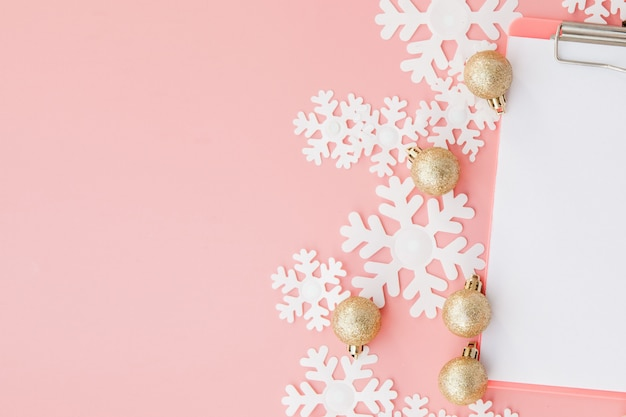 Regalo de navidad en manos de las mujeres y cuaderno en rosa, una vista desde arriba Foto Premium