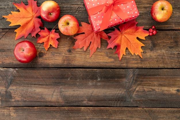Regalo rojo junto a coloridas hojas con espacio de copia Foto gratis