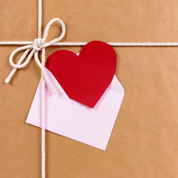 Regalo de san valentín con tarjeta de corazón rojo o etiqueta de regalo, paquete de papel marrón Foto gratis