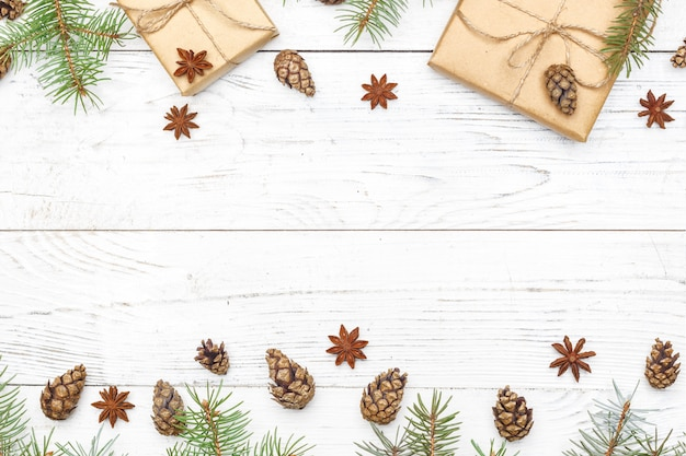 Regalos para año nuevo envueltos en papel artesanal cerca de ramas de abeto y conos sobre fondo blanco de madera vista superior copyspace Foto Premium