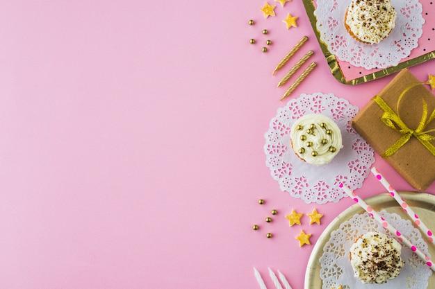 Regalos de cumpleanos; magdalena y velas sobre fondo rosa Foto gratis