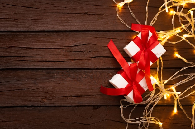 Regalos de navidad en un viejo fondo de madera con textura con bombillas Foto gratis