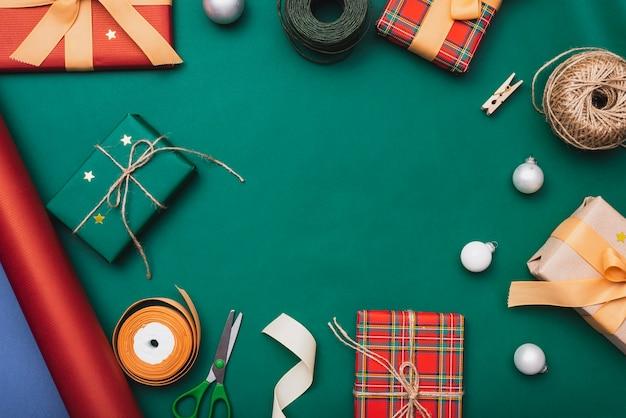 Regalos y otros artículos navideños sobre fondo verde Foto gratis