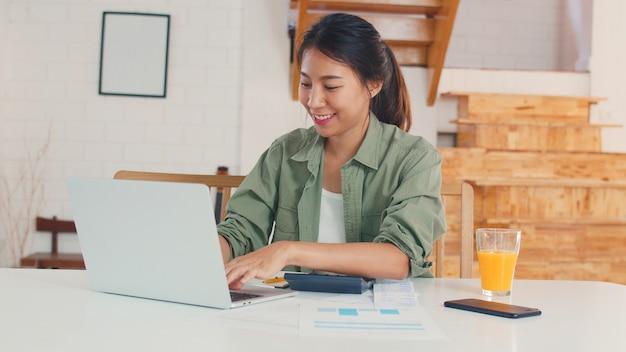 Registros de mujeres asiáticas de negocios de ingresos y gastos en el hogar Foto gratis