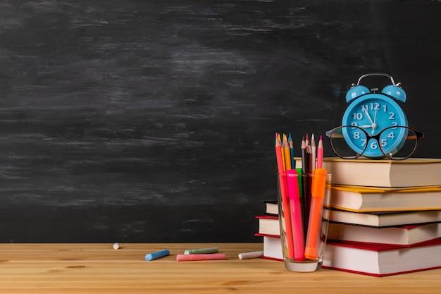 Regreso a la escuela con libros, reloj despertador, anteojos Foto Premium