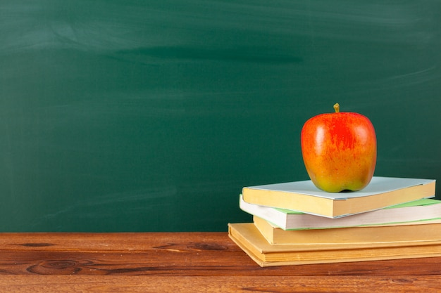 Regreso a la escuela: manzana y libros con lápices y pizarra Foto Premium