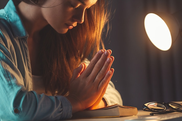 Religión mujer rezando con la biblia en la noche en casa y recurrir a dios, pedir perdón y creer en la bondad. vida cristiana y fe en dios Foto Premium