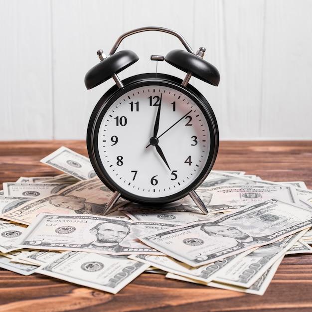 Un reloj de alarma en billetes de la moneda sobre la mesa de madera Foto gratis